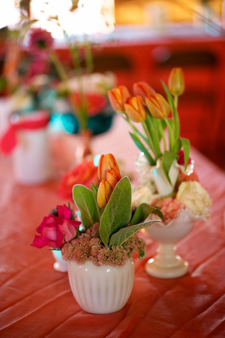 The low tulip centerpieces in milk glass vases offset the higher glass bottle wildflower centerpieces.