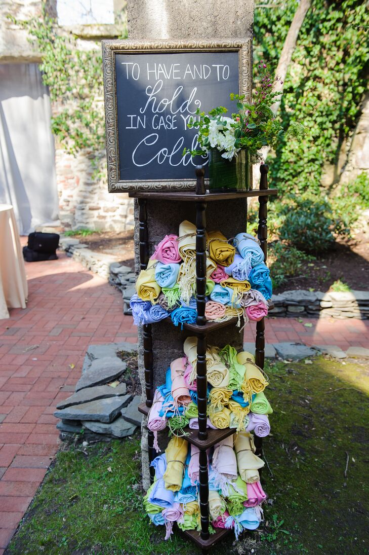 """Since their cocktail hour was outside, Sarah and Tom had a warm gift waiting for their guests. Fringed scarves, ranging in color from blue to lime green, filled a vintage-style bookcase. They decorated the display with a chalkboard sign that read """"To have and to hold in case you get cold."""""""