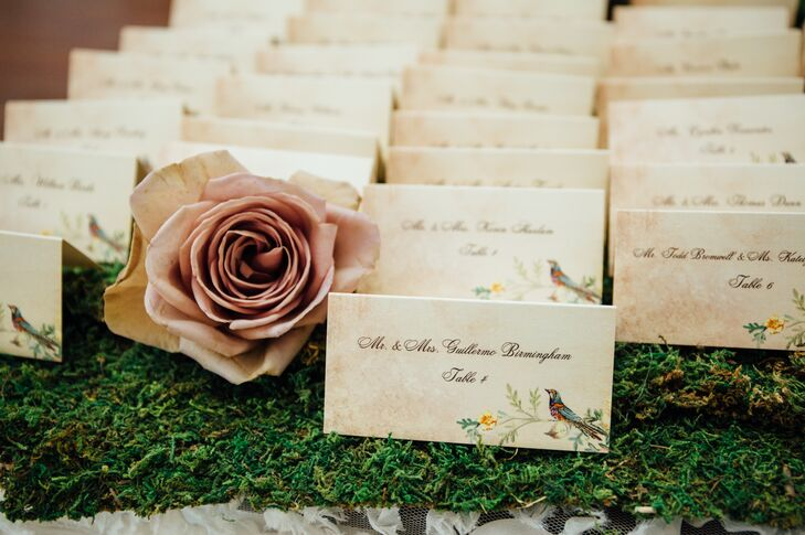 To help their guests find their seats, Jamila and Dennis wrote the name of each guest on antiqued card stock to achieve a vintage-inspired look. The cards were displayed atop a bed of fresh moss to tie into the secret garden theme.