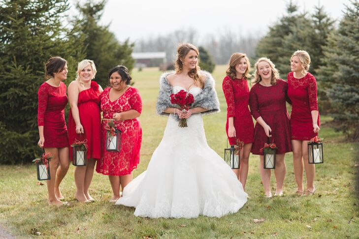 Elizabeth's six bridesmaids wore mismatched knee-length red bridesmaid dresses while carrying rustic lanterns down the ceremony aisle instead of bouquets.