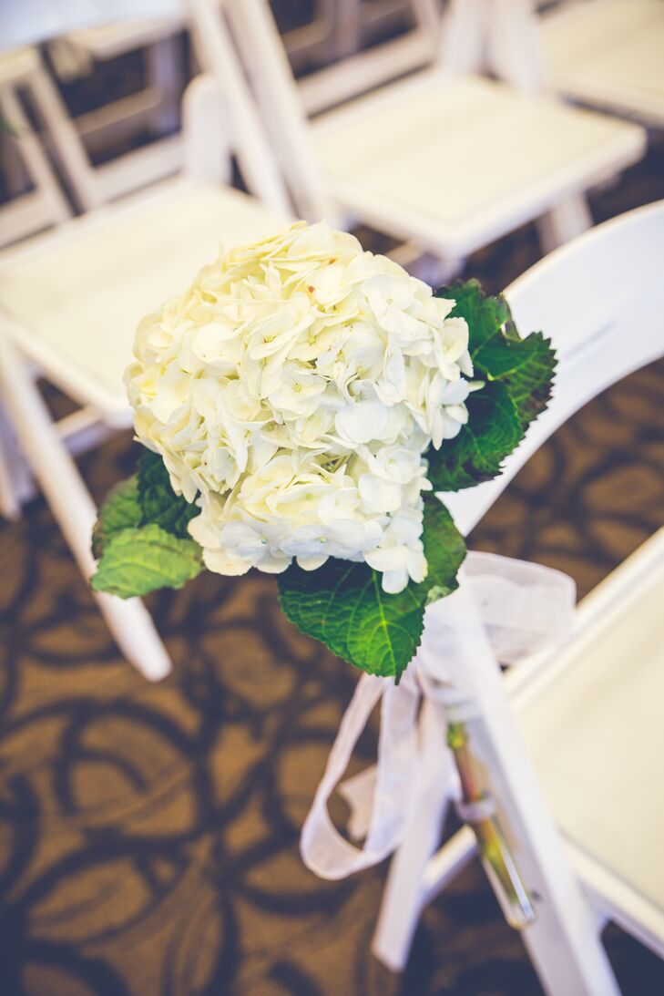 """At the ceremony, white folding chairs lining the aisle were decorated with hydrangea bunches. """"The ceremony decor was very important to me because of how long I waited to marry my groom,"""" Kyra says. """"I wanted that moment to feel elegant and fairy-tale-like."""""""