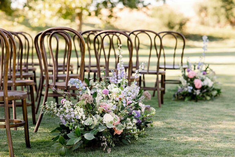 Pastel-hued floral aisle arrangements
