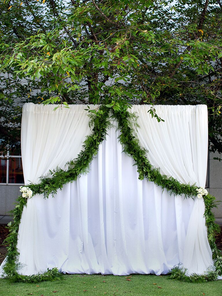 A white curtain arch with simple draped garland