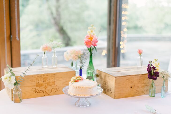 The single-tier ivory cake was accented with fresh flowers on top. The cake was displayed on a simple glass stand, surrounded by wooden boxes and other fresh blooms.