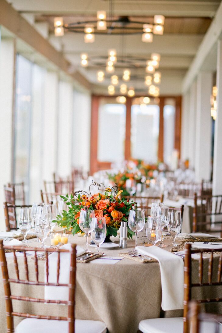 The couple brought their rustic coastal wedding to life with light neutral linens and sunny orange flower arrangements.