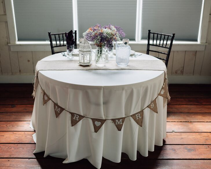 """The sweetheart table was decorated with a burlap table runner, a rustic lantern and a mason jar filled with wildflowers. At the front of the table hung burlap bunting that read """"Mr. & Mrs."""""""