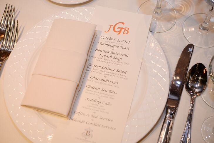 Guests were seated at dining tables for a plated dinner complete with a monogrammed menu card in orange.