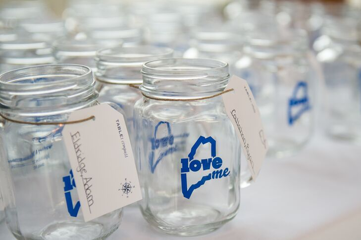 "With a waterfront venue on Maine's rocky coastline, a rustic, nautical theme was a given for Whitney and Mathew's September affair. From the centerpieces to the escort cards and even the menu, each detail played tribute to the wedding's seaside locale. For the escort cards, the couple had special mason jar drinking glasses made with the outline of the state of Maine stamped on each one alongside the expression ""LoveME."" The names of each guest and their seating arrangement were handwritten on vintage gift tags with a compass motif and attached to the glasses."