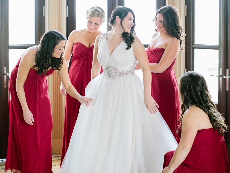 Bridesmaids helping bride before wedding