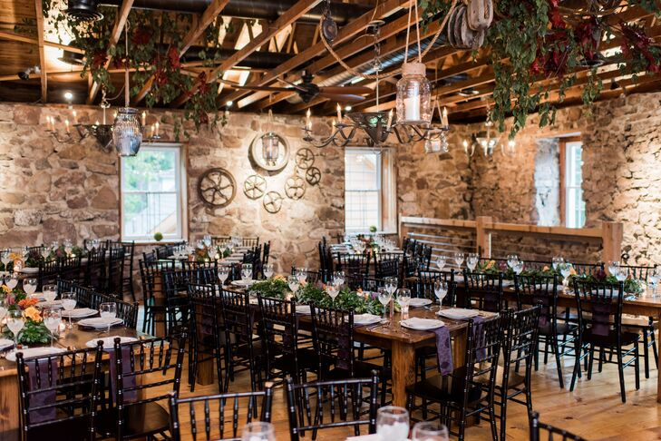 Rustic Reception Space with Black Chiavari Chairs and Hanging Greenery