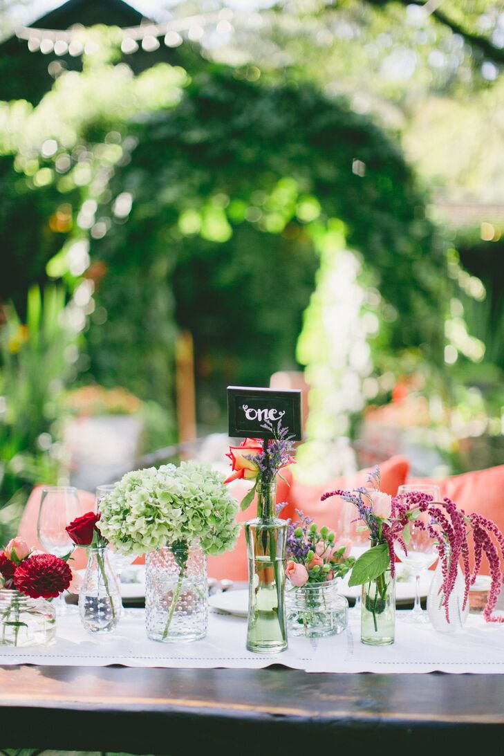 """""""We wanted the tables to be simple and colorful,"""" Melanie says. Rustic wooden farm tables were topped with linen runners and vases in various shapes and sizes and were filled with seasonal blooms."""