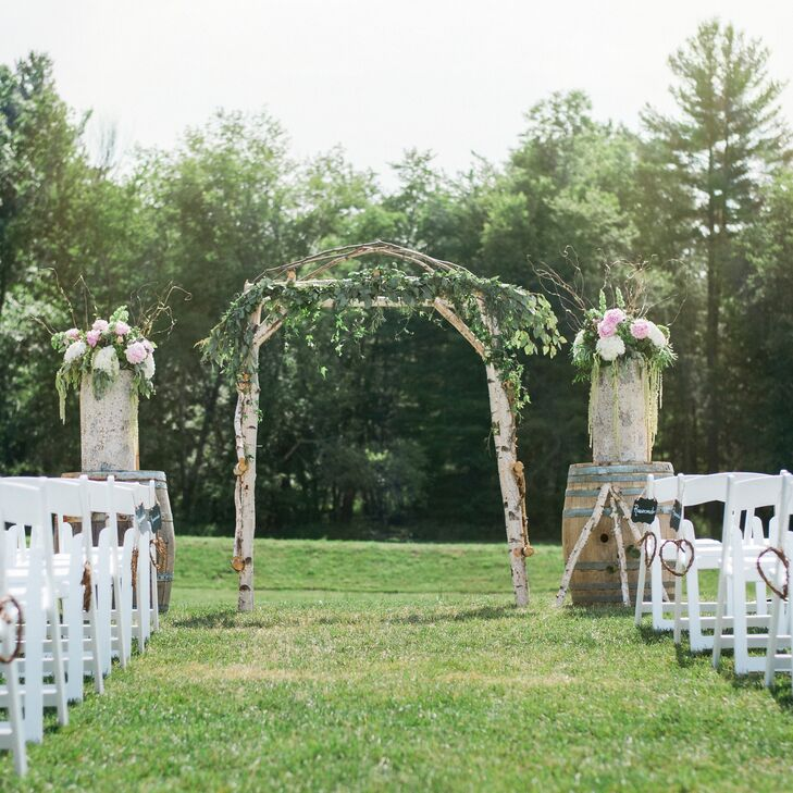 A rustic arch made of branches stood at the end of the ceremony aisle.