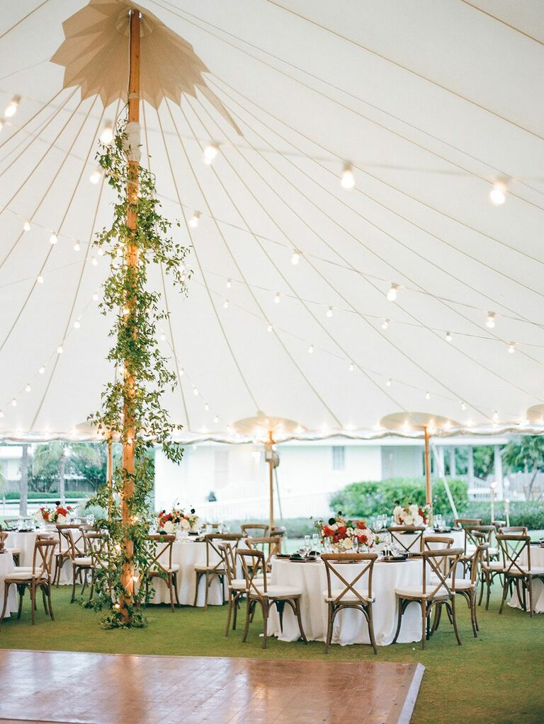Center pole of tall wedding tent covered with garlands of greenery