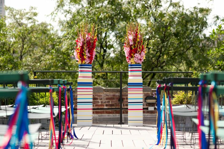 Bold, modern pillars held bunches of gladiolus, while different-colored ribbons decorated the chairs lining the ceremony aisle.