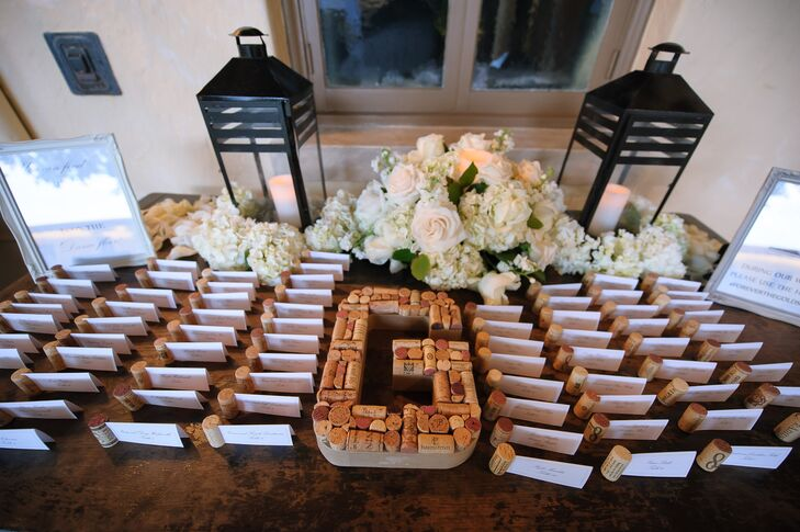 For a fun and unexpected twist, the couple decorated their escort-card display with wine corks. Each of the Melissa and Derek's 125 escort cards was paired with a wine cork, and the same accents formed their initial. Black lanterns and lush white florals also lined the table and complemented their centerpieces inside the reception.