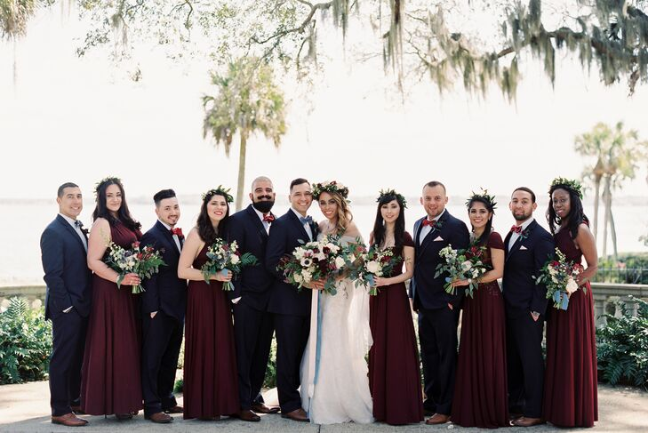"Bridesmaids wore crimson gowns with convertible necklines. ""This way they all had a cohesive look but could still showcase their individuality,"" Tammie says. Groomsmen donned classic dark navy tuxedos."