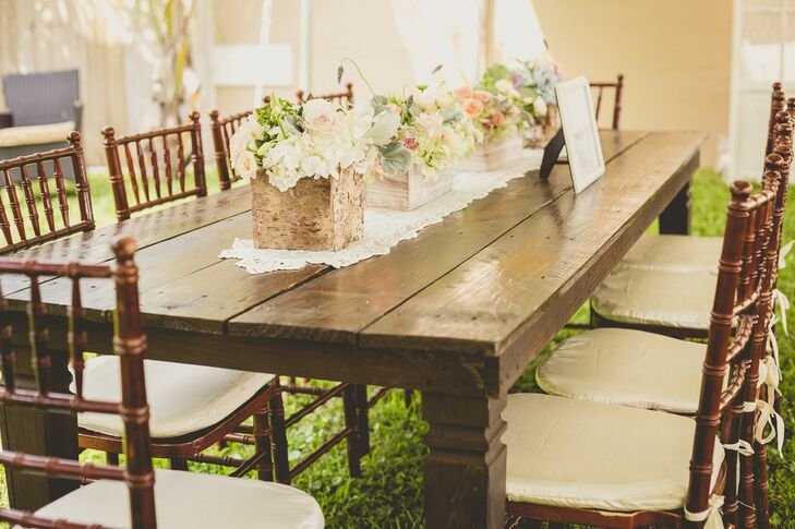 """""""Our furniture had so much character that I didn't want to clutter them with huge centerpieces,"""" Roxy says. Instead, they highlighted each wooden table with classic ivory lace runners and low centerpieces. The tablescapes were filled with wooden breakaway boxes of ivory roses, white hydrangeas, green hypericum and pink garden roses from Flowers International Events."""