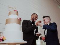 Same-sex couple feeding each other slices of wedding cake