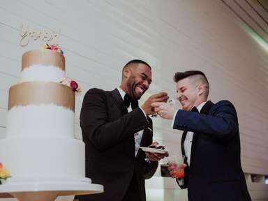 Same-sex couple feeding each other slices of wedding cake