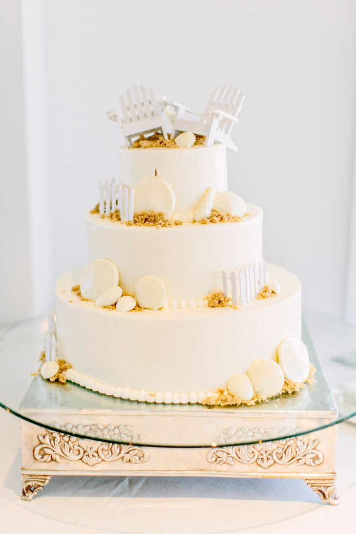 In addition to a make-your-own ice cream cookie sandwich bar, Louise and Katie treated guests to a decadent slice of wedding cake. The three-tiered confection featured a beach motif, complete with crumbled biscuit sand, white chocolate seashells and miniature Adirondack beach chairs. Beneath each layer of buttercream frosting were flavors like red velvet cake with white chocolate mousse filling and golden vanilla cake with strawberry and champagne mousse filling.