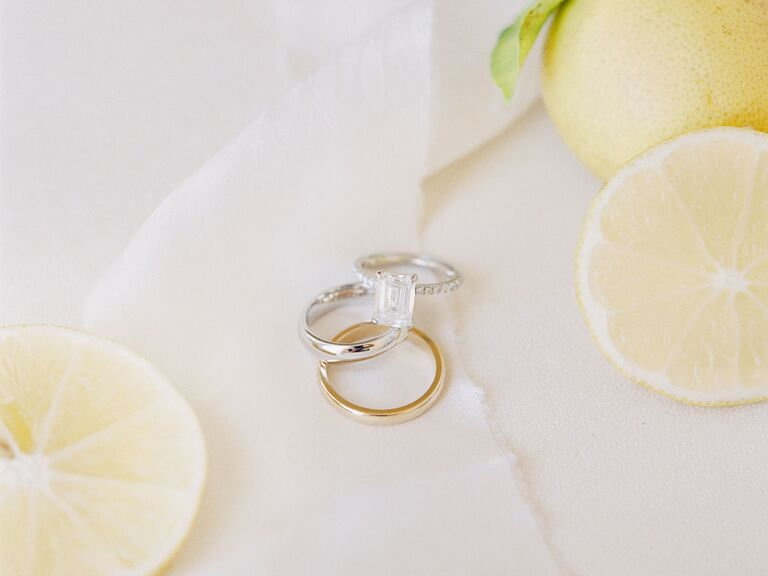 Wedding bands and engagement ring flatlay with citrus