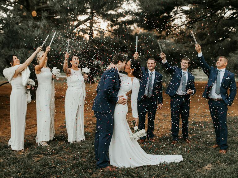 Bridesmaids and groomsmen tossing confetti over bride and groom