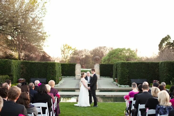 The couple exchanged vows outdoors surrounded by a reflecting pool and hedges.