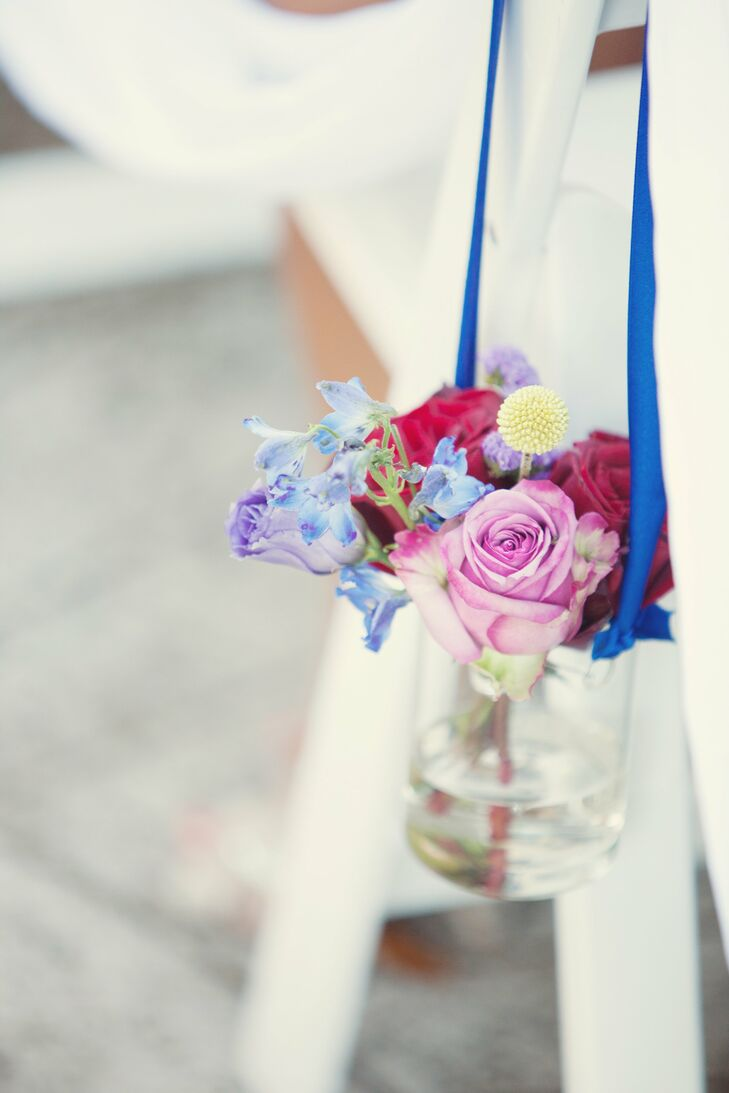 Glass jars filled with roses and craspedia hung from the ceremony chairs.
