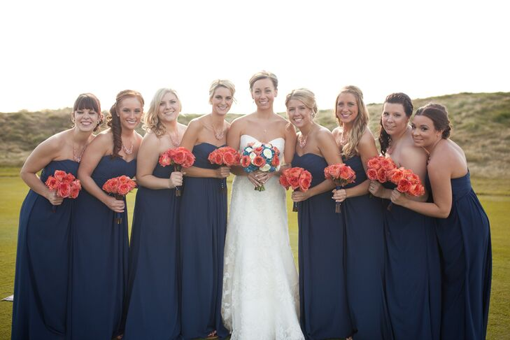8072111fc327 The bridesmaids accented their navy dresses with coral rose bouquets.