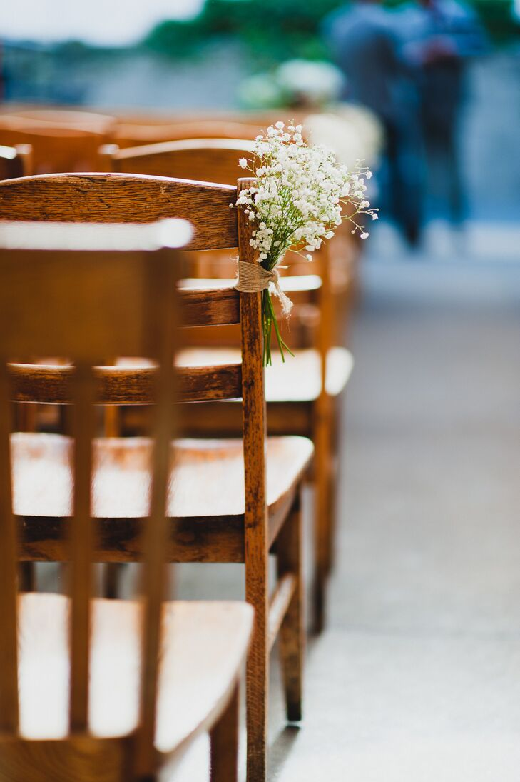 Wood chairs at the ceremony were decorated with small baby's breath arrangements.
