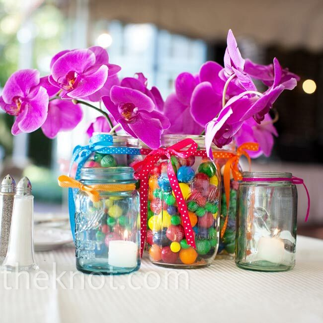 The tables were topped with Mason jars in varying sizes, which were tied with ribbons and filled with gumballs, votive candles, and bright pink phaelenopsis orchids.