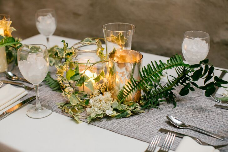 Amy Young of Leaves of Grass Floral Design was instrumental in the wedding's design and transformed the raw industrial event space at Front and Palmer in Philadelphia, Pennsylvania, into an inviting and intimate backdrop. Warm candlelight incorporated throughout infused the room with undeniable ambiance, while natural elements like vines, ferns and an assortment of wispy pale blue and white wildflowers gave the decor a rustic, organic edge.