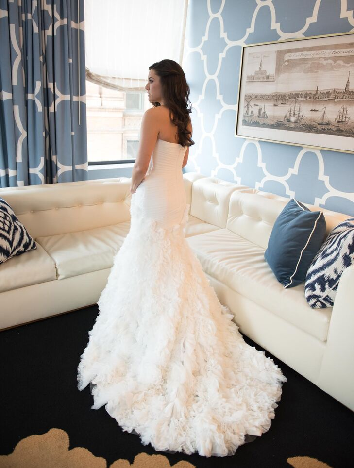 Karen wore a strapless Enzoani gown in a fit-and-flare silhouette with a sweetheart neckline. The dress' focal point was its modern, ruffled skirt and train that paired beautifully with the fitted and ruched bodice. Karen went with a romantic hairstyle, worn down with curls.