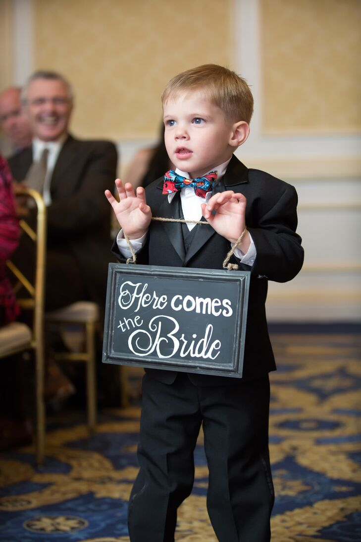 "A child attendant carried a small sign down the aisle that said ""Here Comes the Bride."""
