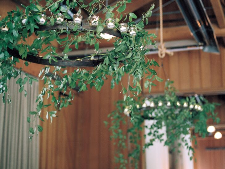 The design team accentuated all the raw wood in the reception room by installing iron light fixtures lined with organic greenery.