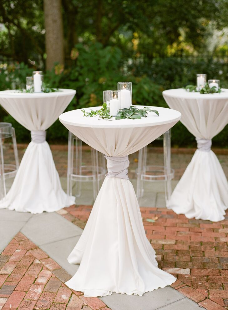 White Pillar Candles and Greenery Atop Cocktail Tables