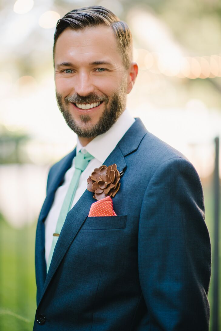 """The groom wore a navy suit with a mint green tie, a coral pocket square and a leather flower lapel pin. He also wore a silver tie clip engraved with """"Forever."""""""