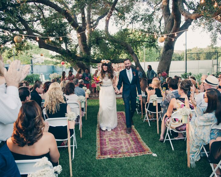 The couple was married under an old oak tree with a backdrop of brightly colored ribbons. A vintage rug lined the aisle and overhead string lights and gold paper lanterns added ambience.