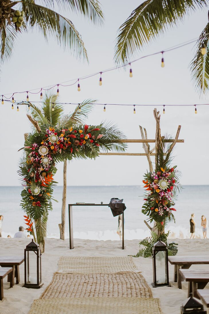Beach Ceremony Site with Flower-Covered Arch and String Lights
