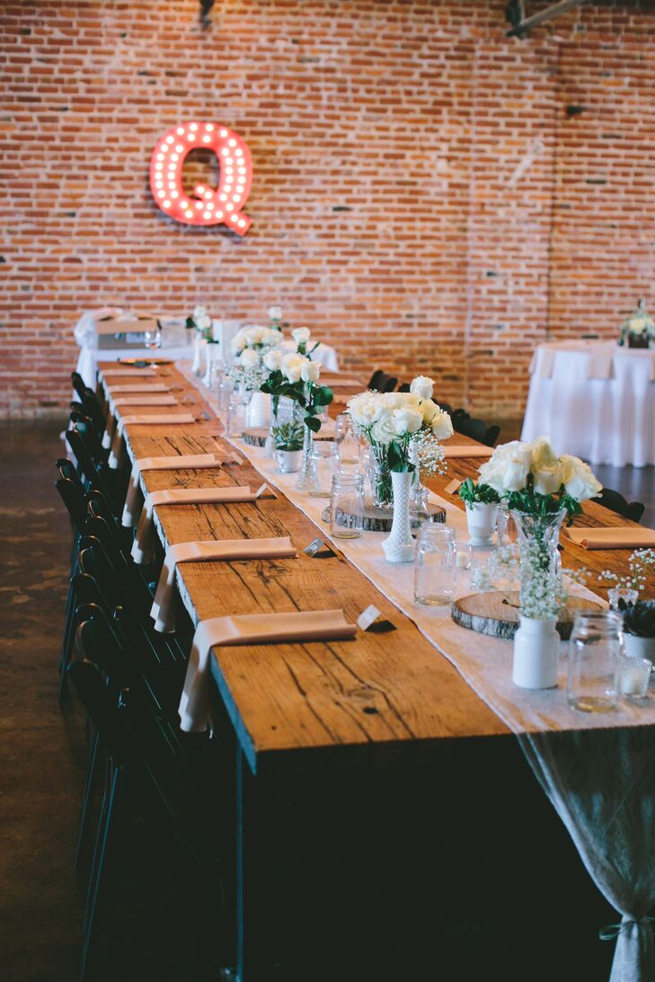 The Guild of Kansas City, Missouri, had an old-world charm and an industrial feel that inspired much of the decor, from the palette of earth tones and metallics to the wooden accents and antiques. For the reception the couple used a mix of long and round tables and created different tablescapes for each. Vintage milk glass vases filled with an assortment of full white blooms and delicate lace table runners had a distinct ladylike elegance that balanced out the rustic feel of long wooden farm tables.