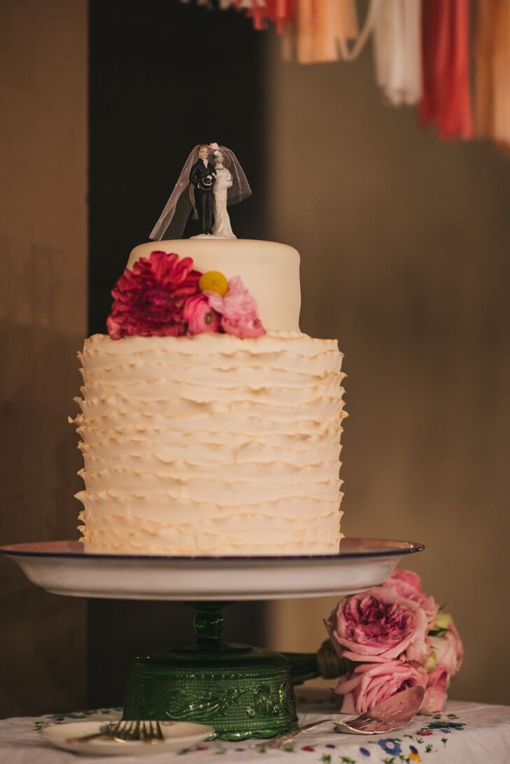 The wedding cake featured an extra tall bottom tier with uplifting ruffles and a smooth top tier with a classic bride and groom cake topper. Brightly colored flowers rested on one side.