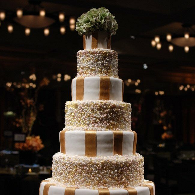 Andrea and Matt's wedding cake featured seven tiers covered in alternating patterns of gold and ivory sugar balls and thick gold stripes of fondant. Inside, the flavors alternated between traditional Italian cream and white chocolate truffle torte.