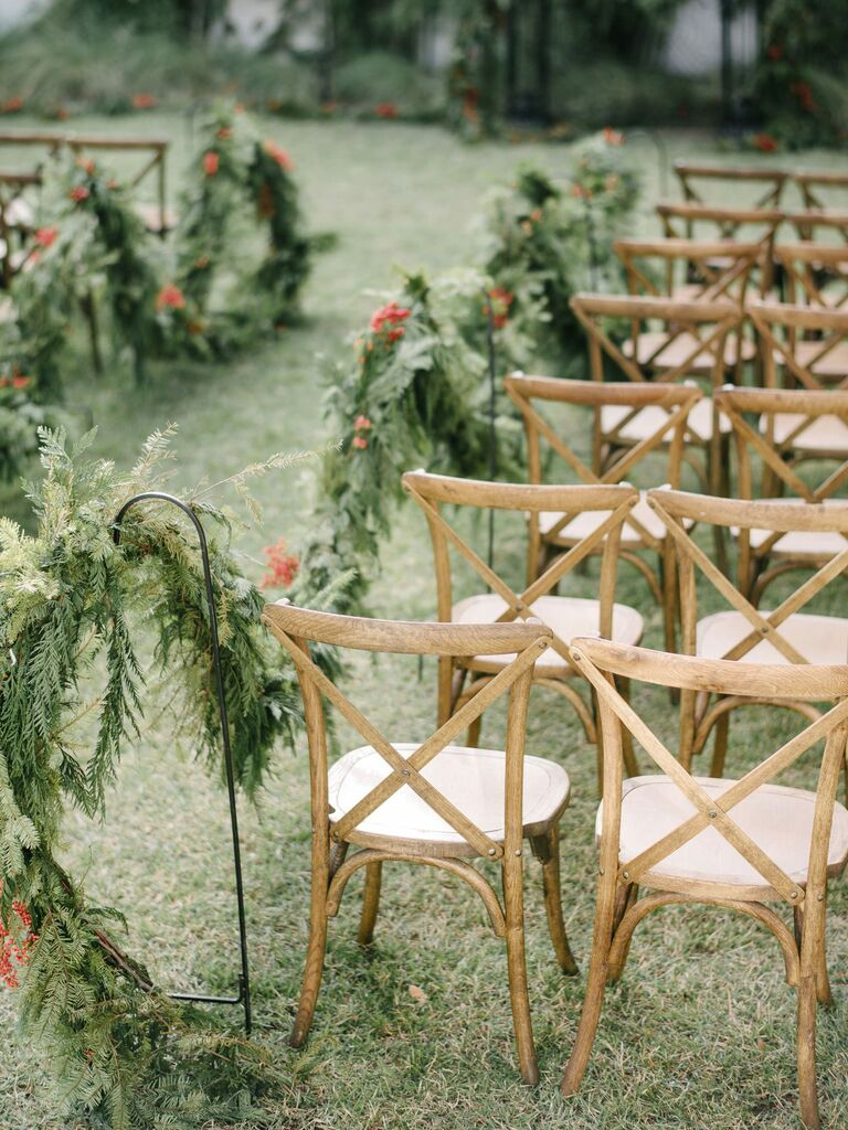 Outdoor winter wedding ceremony with garland aisle decor