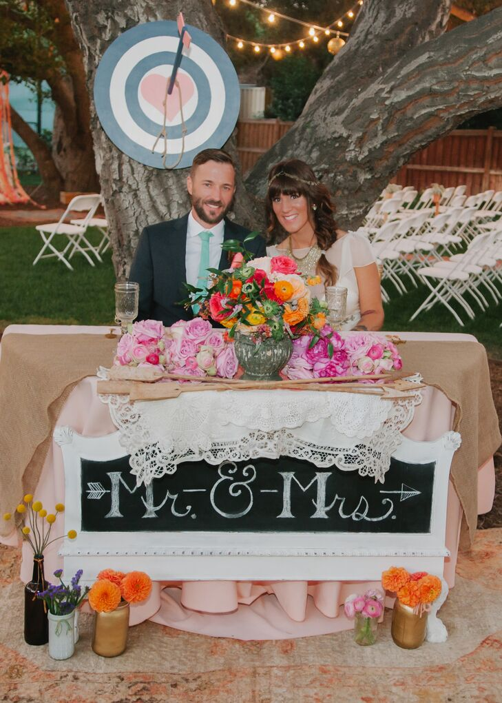The sweetheart table carried a Cupid's arrow motif with an arrow striking a heart dart board on the tree behind them wooden arrows at the front of their table.