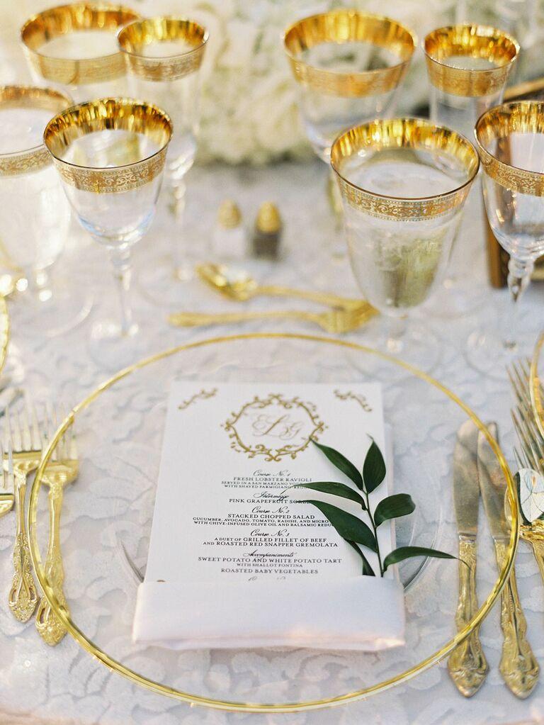 Elegant gold rimmed glassware and dinnerware at regencycore wedding reception