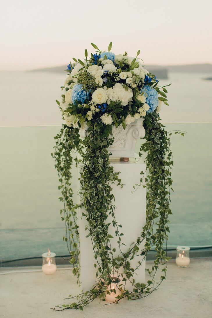 The couple chose white carnations and roses, cascading green ivy and blue hydrangeas to decorate the outdoor reception.