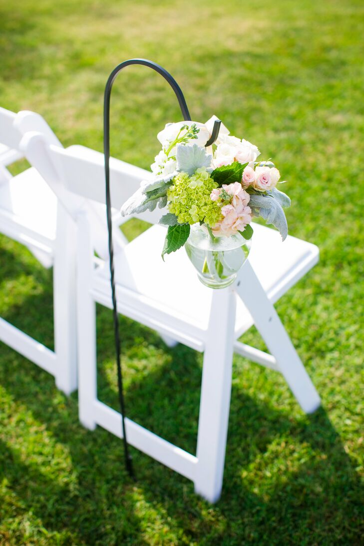 Haley had the aisle leading to the altar lined with long black shepherd's hooks. On each hook hung a glass vase of blush-and-white-colored flowers matching the bouquets.