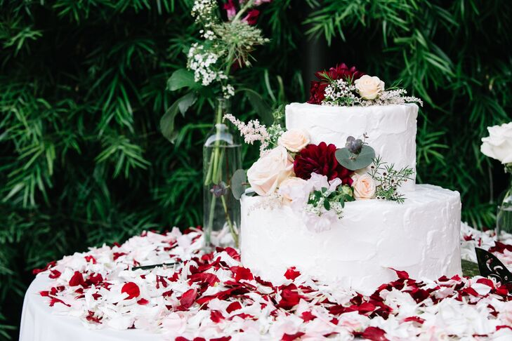 The simple yet elegant two-tier cake featured rustic ivory frosting and live floral accents.