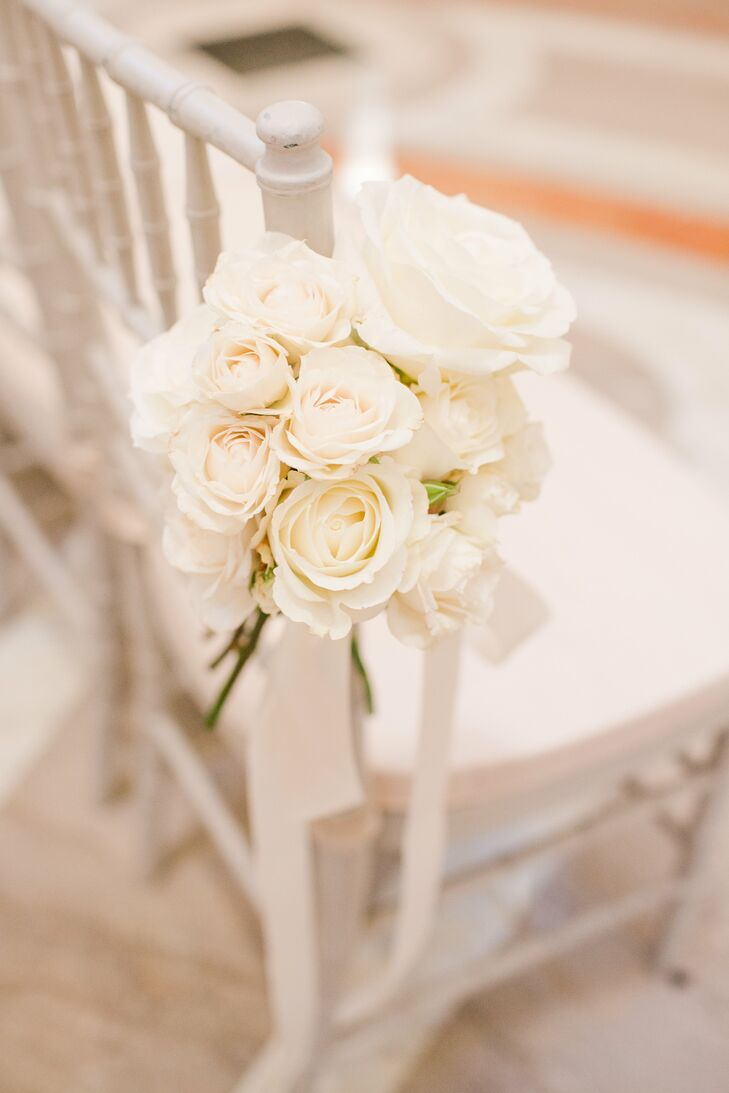 The white chiavari chairs on the ceremony aisle were decorated with bundles of white roses tied together with white satin ribbon.