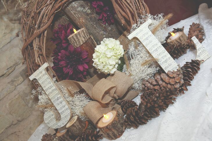 The reception was decorated with wooden letters decorated with sheet music, burlap bows, pine cones and branch wreaths for a rustic look to match the fall wedding.